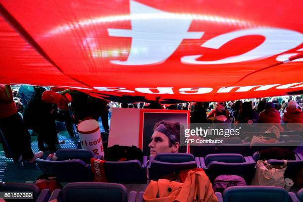 A poster of Roger Federer of Switzerland is seen on a chair under a huge flag waved by his fans during the men's singles final match against Rael...