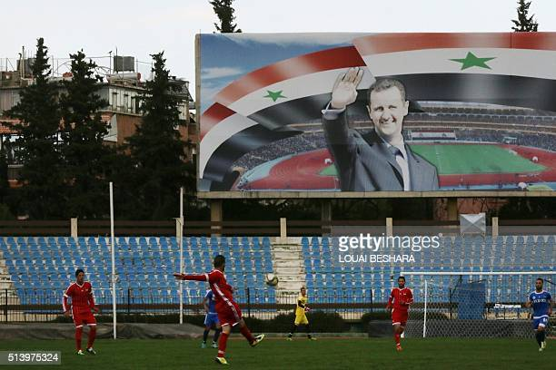 A poster of Syrian President Bashar alAssad is seen during a football game between Latakia's Hutteen and Hama's Taliya as part of the Syrian league...