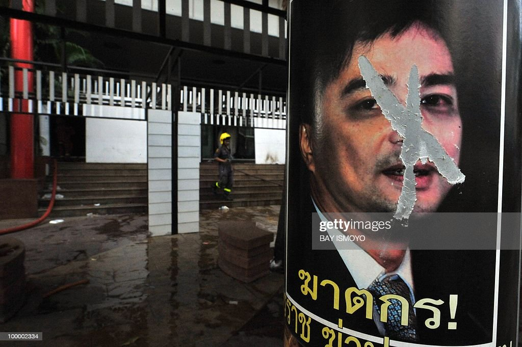 A poster of Thai Prime Minister Abhisit Vejjajiva is seen as firefighters extinguish the remaining smouldering area near the TV3 television station on Rama IV boulevard in downtown Bangkok on May 20, 2010. Plumes of smoke hung overhead as Bangkok emerged from an curfew aimed at quelling mayhem unleashed by enraged anti-government protesters targeted in an army offensive on May 2010.