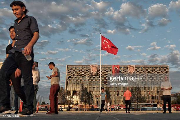 A poster of Turkey's President Recep Tayyip Erdogan hangs on Ataturk Cultural Center as people walk at Istanbul's central Taksim Square on July 18...