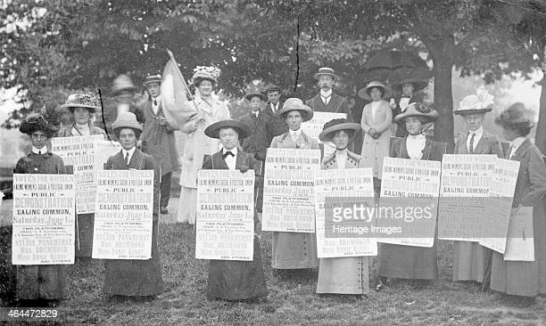A 'poster parade' of Ealing suffragettes advertising a meeting to be held on Ealing Common 1st June 1912 Wearing sandwich boards advertising the...