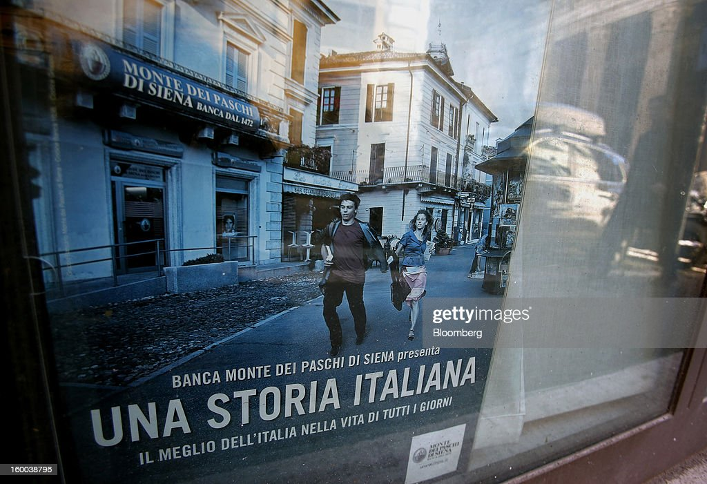 A poster reading 'Banca Monte dei Paschi Di Siena presents: An Italian Story: The Best of Italy in Everyday Life' sits on display in the window of the company's bank branch in Rome, Italy, on Friday, Jan. 25, 2013. Italian Prime Minister Mario Monti said the Bank of Italy will take another look at Banca Monte dei Paschi di Siena SpA's books after the company disclosed this week it may face more than 700 million euros of losses related to structured finance transactions hidden from regulators. Photographer: Alessia Pierdomenico/Bloomberg via Getty Images