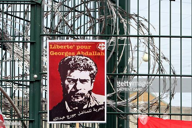 A poster reading 'Freedom for Georges Abdallah' is placed near razor wire on the gate outside the prison in Lannemezan southern France on October 25...