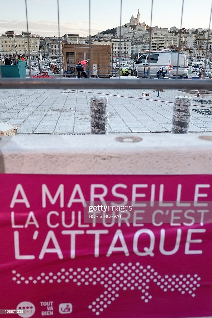 A poster reading ' In Marseille, culture on the attack' hangs on a barrier surrounding the construction site to increase the pedestrian access in the Vieux-Port district in Marseille, southern France, on January 2, 2013, as part of urban renewal for the 2013 'Marseille-Provence European Capital of Culture' event. HORVAT