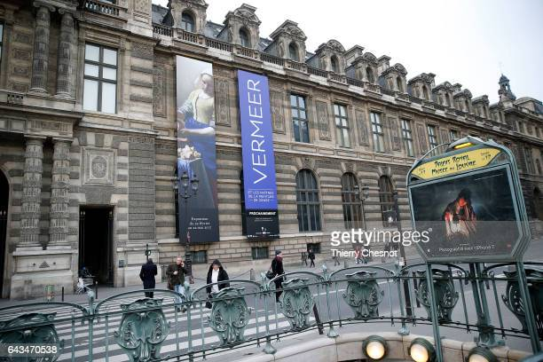 A poster representing the painting 'The Milkmaid' by Dutch painter Johannes Vermeer is seen on the facade of the Louvre museum during the exhibition...