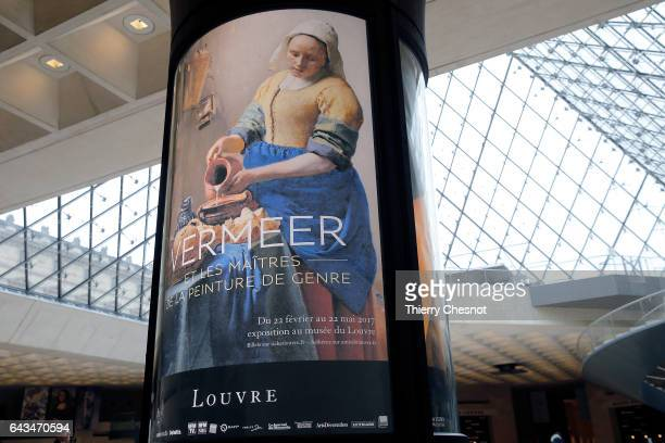 A poster representing the painting 'The Milkmaid' by Dutch painter Johannes Vermeer is seen in the Louvre museum during the exhibition 'Vermeer and...