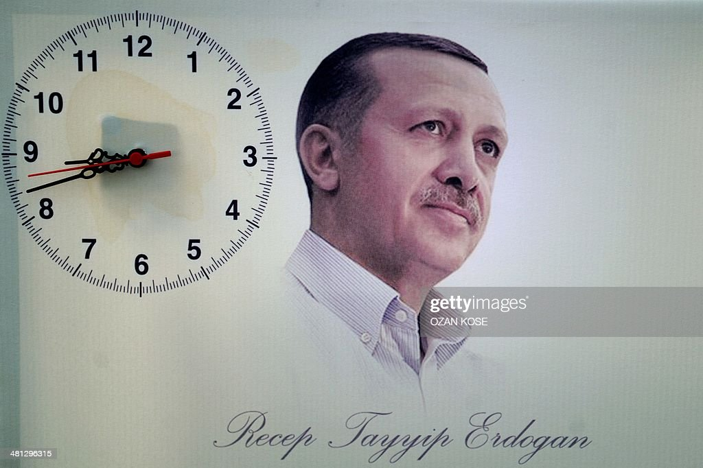 A poster showing Turkish Prime Minister Recep Tayyip Erdogan is seen next to a hanging clock during a rally of the Justice and Development Party (AKP) in the Maltepe district at the asia side of Istanbul on March 29, 2014. Turkey gears up for local elections on March 30 ahead of a presidential vote in six months and parliamentary polls next year. Erdogan and his Islamic-leaning party, after over a decade in power, face the first electoral test following months of political turmoil, with mass street protests and a corruption scandal spread via Twitter, Facebook and YouTube. Amid an atmosphere of distrust ahead of tomorow's election with over 50 million eligible voters, the CHP and tens of thousands of citizen volunteers plan to monitor the ballot count.
