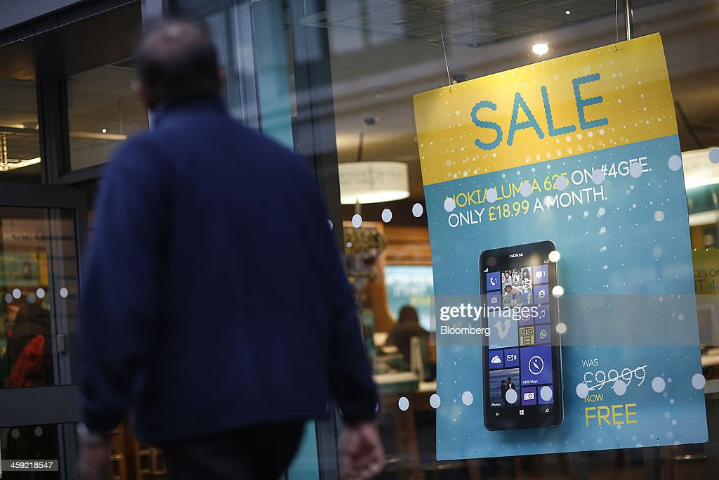 A poster sits in a window advertising a Nokia Lumia 625 Windows smartphone, manufactured by Nokia Oyj, as a pedestrian passes an EE mobile phone store in London, U.K., on Tuesday, Dec. 24, 2013. Vodafone Group Plc; EE, which is co-owned by Orange SA and Deutsche Telekom AG; Three, owned by Hutchison Whampoa Ltd.; and Virgin Media Inc. said they will cap bills run up on phones reported lost or stolen, stop mid-contract price increases, and support the U.K. government in its attempt to end roaming charges within the European Union. Photographer: Simon Dawson/Bloomberg via Getty Images