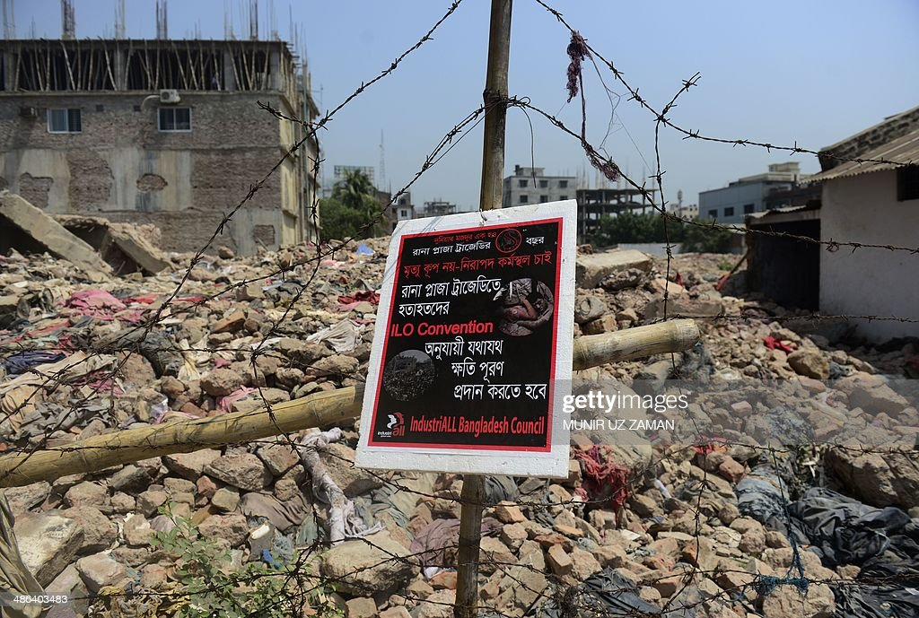 A poster tied to a fence at the scene of the Bangladesh Rana Plaza building collapse and reading, 'We want a safe work place, not a death trap' is seen on the first anniversary of the disaster on the outskirts of Dhaka on April 24, 2014. The Rana Plaza building collapsed on April 24, 2013, killing 1138 workers in the world's worst garment factory disaster. Western fashion brands faced pressure to increase help for victims as mass protests marked the anniversary. Thousands of people, some wearing funeral shrouds, staged demonstrations at the site of the now-infamous Rana Plaza factory complex. AFP PHOTO / Munir uz ZAMAN