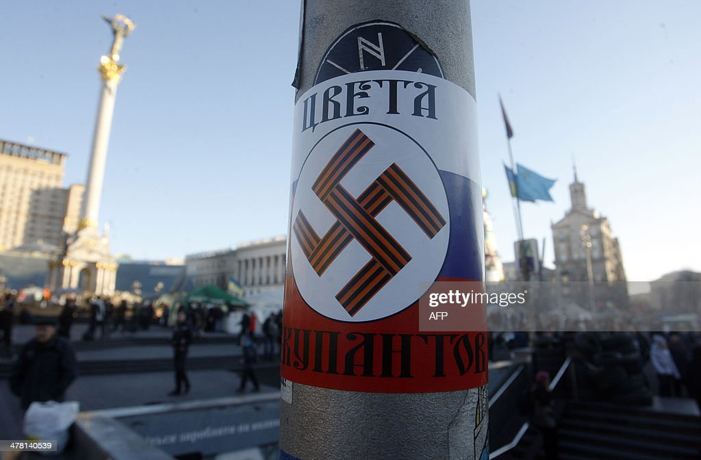 A poster with a Nazi swastika printed on a Russian flag and reading 'The colours of the occupiers' has been glued on Independence Square in Kiev on March 12, 2014. Russia will mirror any visa sanctions the European Union imposes on its lawmakers, a senior parliamentarian said Wednesday, as Moscow and the West slug it out diplomatically over the crisis in Ukraine.