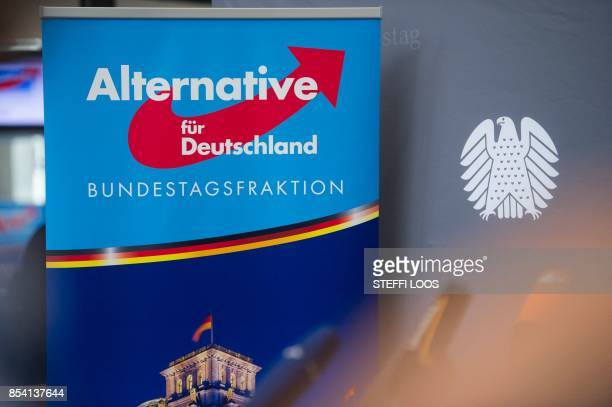 A poster with AfD logo is pictured next to a Bundestag background banner in front of parliamentary group room where the first meeting of the...