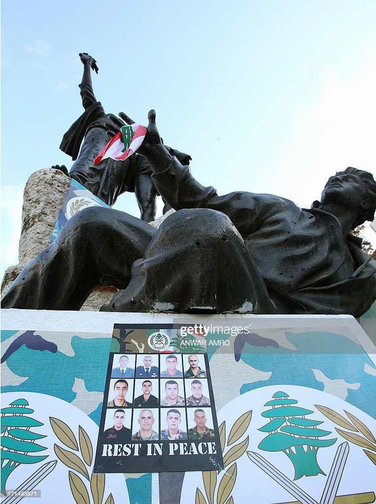 A poster with images of some of the 17 Lebanese Army soldiers killed in clashes with supporters of radical Sunni cleric Ahmad al-Assir, is posted under the statue in Martyr's Square, downtown Beirut on June 25, 2013, during a rally to show support for the army a day after the soldiers died in fighting in the southern port city of Sidon.