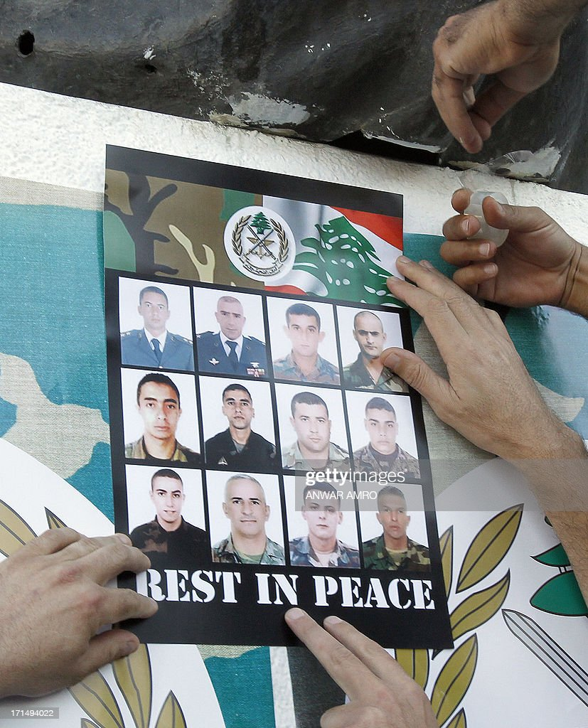 A poster with images of some of the 17 Lebanese Army soldiers killed in clashes with supporters of radical Sunni cleric Ahmad al-Assir, is posted under the statue in Martyr's Square (top useen), downtown Beirut, on June 25, 2013, during a rally to show support for the army, a day after the soldiers died in fighting in the southern port city of Sidon.