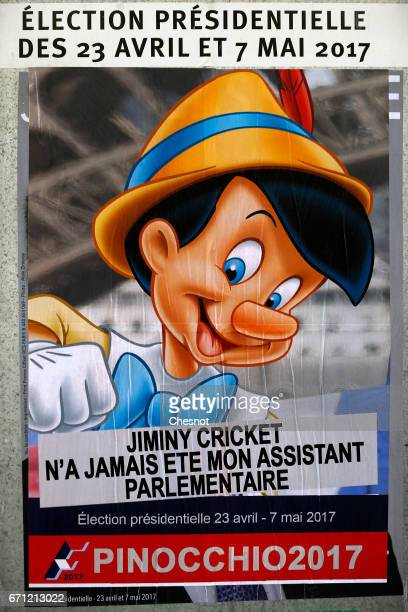 A poster with the Disney character Pinocchio is fixed over the official poster of French presidential candidate Jean Lassalle one of the 11...