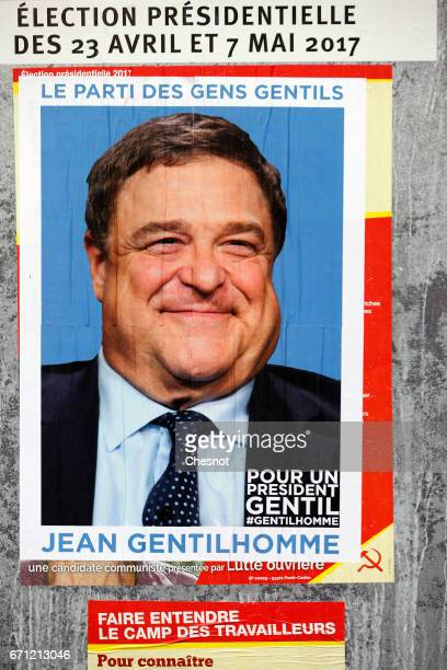 A poster with the face of actor John Goodman is fixed over the official poster of French presidential election candidate for the farleft 'Lutte...
