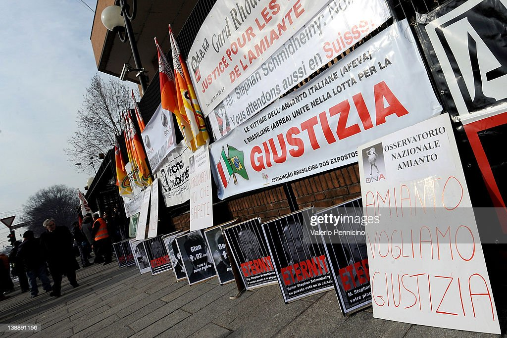 Posters ad flags are displayed outside Turin courthouse during Eternit final verdict on February 13, 2012 in Turin, Italy. The Turin court has convicted Swiss billionaire Stephan Schmindheiny and Belgian baron Jean-Louis de Cartier for 16 years each after they were accused of involuntary manslaughter and disregard for workplace safety regulations, after a three year trial. Around 1500 relatives and friends of the alleged 3000 victims attended the final day of the trial with 160 foreign delegations attending from all over the world.