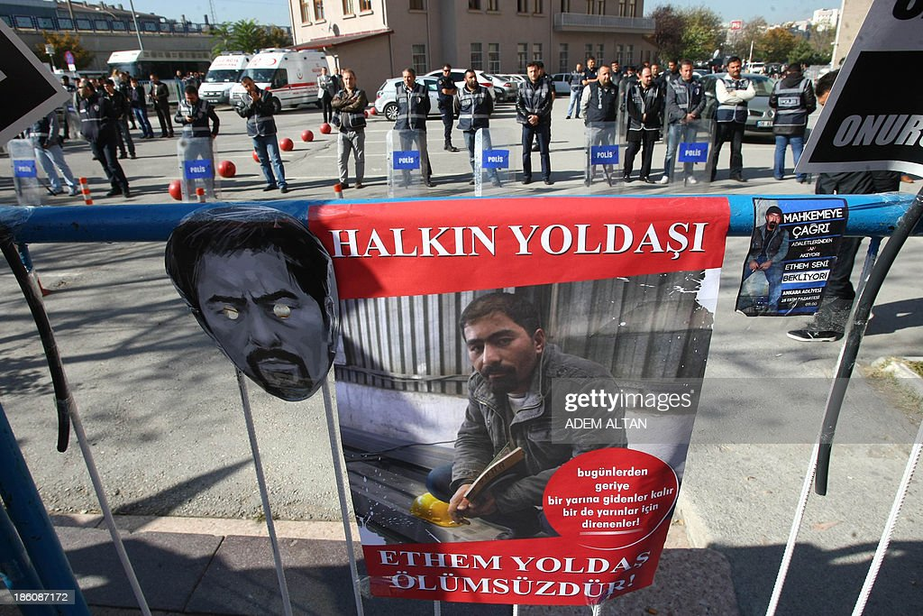 Posters and a mask of Ethem Sarisuluk, a Turkish protester who was killed during clashes in June, are placed on a barricade opposite policemen on October 28, 2013 during a demonstration in Ankara against a court's refusal to detain a policeman accused of killing Sarisuluk. A police officer identified only as Ahmet S. is on trial accused of shooting to death the 26-year-old protester during mass anti-government street protests in Ankara in June. The Ankara court rejected a demand by the victim's lawyers that the defendant be detained and ruled instead that he could take part in hearings via video conference for security reasons.