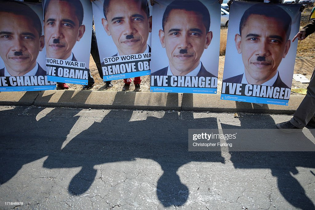 Posters depicting a likeness of <a gi-track='captionPersonalityLinkClicked' href=/galleries/search?phrase=Barack+Obama&family=editorial&specificpeople=203260 ng-click='$event.stopPropagation()'>Barack Obama</a> are held by protesters outside Johannesburg University in Soweto in advance of President Obama's meeting with students later today on June 29, 2013 in Johannesburg, South Africa. This is Obama's first official visit to South Africa, and is holding bilaterial meetings with President Jacob Zuma, and also meeting with students in Soweto Township. During his tour the president will also visit Robben Island, where former President Nelson Mandela spent some of his 27 years in prison for fighting against apartheid.