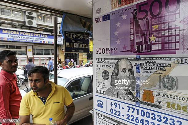 Posters depicting a US one hundred dollars banknote bottom and a 500euro banknote are displayed on a wall near a currency exchange in Mumbai India on...