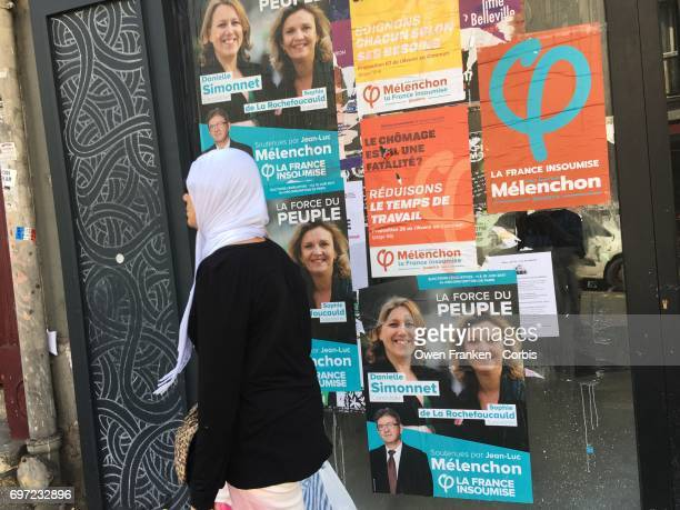 Posters for legislative candidates cover the wall in the multi ethnic 20th arrondissement of Paris France