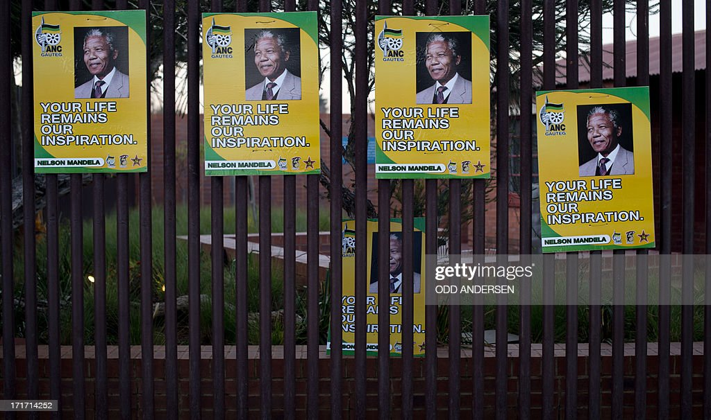 ANC posters in honour of Nelson Mandela reading 'Your Life Remains Our Inspiration' hang on the fence outside his house in the township of Soweto on June 27, 2013. Ailing South Africa's former president Mandela is receiving treatment at the Mediclinic heart hospital in Pretoria. Messages of support poured in from around the world for the Nobel Peace Prize winner, who spent 27 years behind bars for his struggle under white minority rule and went on to become South Africa's first black president.