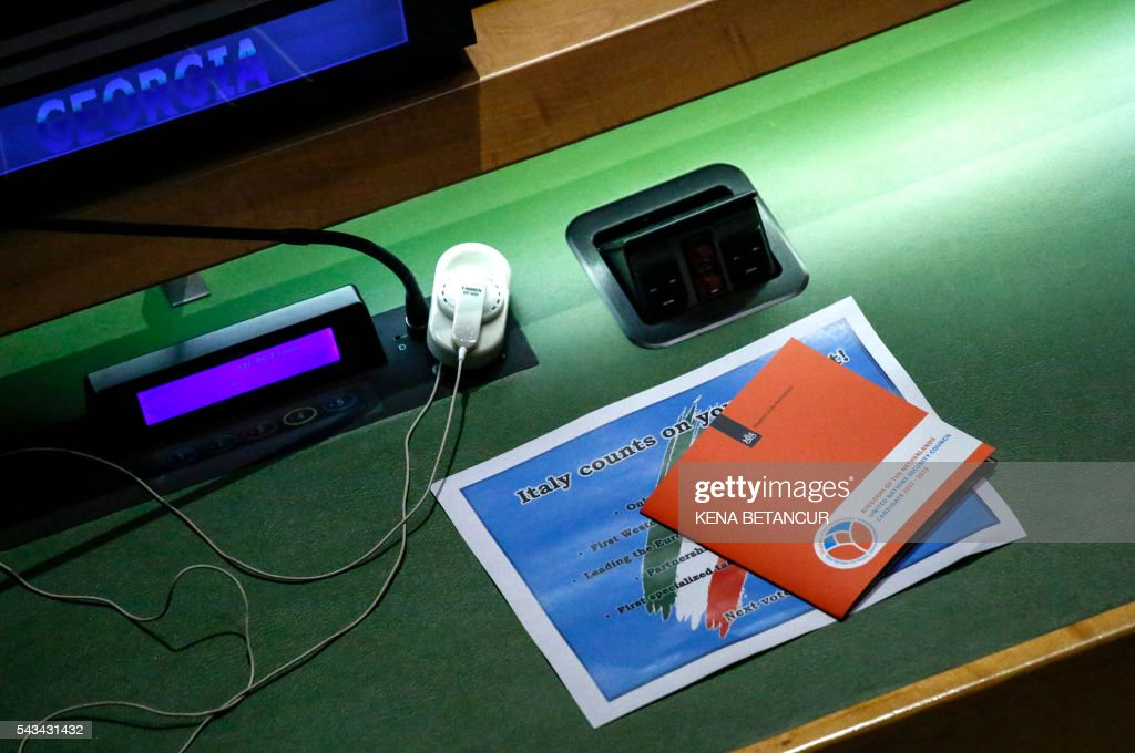 Posters left by Italians and Dutch to promote their countries rest on the empty table of Georgia before the fourth roundof voting in the Election of five non-permanent members of the Security Council at the United Nations in New York on June 28, 2016. / AFP / KENA