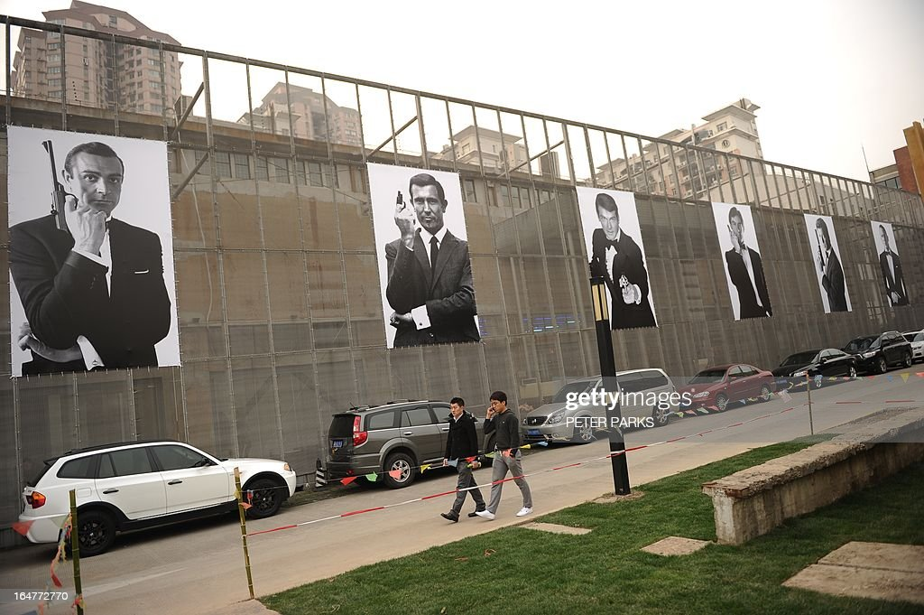Posters of actors who have played James Bond are seen outside an exhibition on the fictional British spy in Shanghai on March 28, 2013. The exhibition opened in Shanghai just weeks after the Communist government's censors cut parts of the latest film in the franchise, 'Skyfall' with a scene showing prostitution in Macau, a special administrative region of China, was removed, as was a line in which Bond's nemesis mentions being tortured by Chinese security agents. AFP PHOTO/Peter PARKS