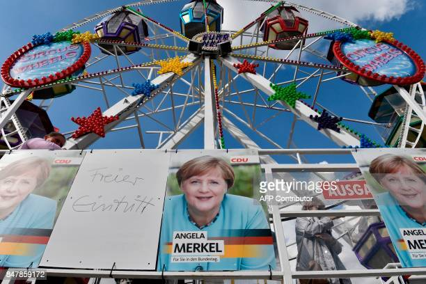 Posters of German Chancellor Angela Merkel are pictured next to a Ferris wheel as she continues on the election campaign trail in Stralsund on...