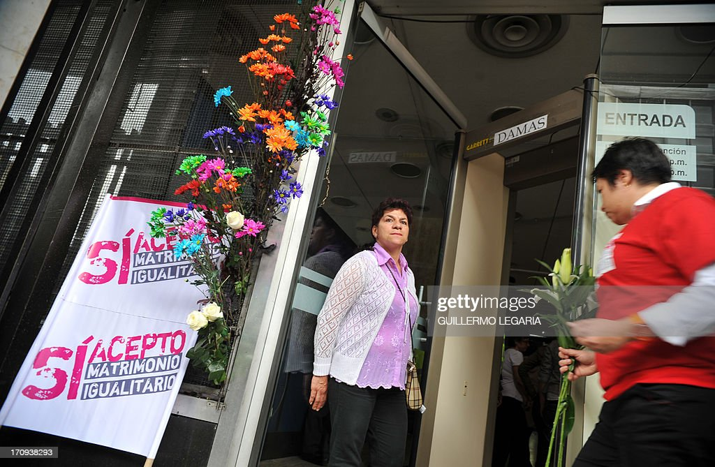 Posters that read, 'yesf I agree, equalitarian marriage' and flowers adorn the entrance of the courthouse in Bogota, Colombia, on June 20, 2013, as gay couples fill documents to apply for registration of their marriage. From today Colombia will enter into a legal puzzle on gay marriage, as gay couples will go to notaries and judged without knowing if they will come out with the document as desired, given the legal vacuum that persists for such unions. AFP PHOTO/Guillermo LEGARIA