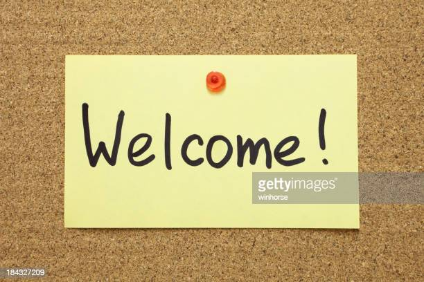 Post-it note with welcome written on board with pushpin
