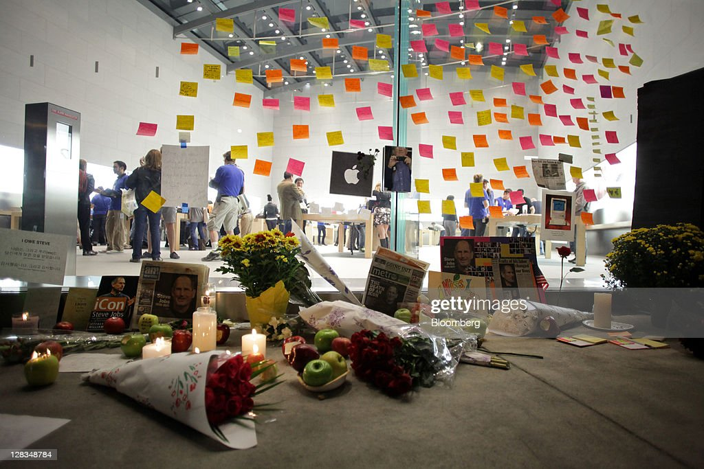 Post-it notes, flowers and messages are left at a memorial for Steve Jobs, co-founder and former chief executive officer of Apple Inc., outside an Apple store in New York, U.S., on Thursday, Oct. 6, 2011. Jobs, who built the world's most valuable technology company by creating devices that changed how people use electronics and revolutionized the computer, music and mobile-phone industries, died on Oct. 5. He was 56. Photographer: Stephen Yang/Bloomberg via Getty Images