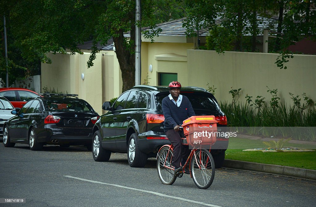 A postman cycles past the residence of Nelson Mandela in Johannesburg on December 27, 2012. South Africa's anti-apartheid icon Nelson Mandela was recovering at his Johannesburg home today, convalescing and receiving further care after a nearly three-week hospital stay, officials said. SAFODIEN