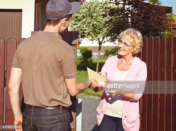Postman delivering a letter for senior lady
