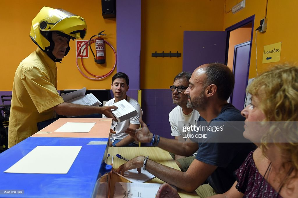 A postman (R) delivers a postal vote pack for Spains general election to scrutineers at a polling station in Hospitalet, near Barcelona on June 26, 2016. Spain votes today, six months after an inconclusive election which saw parties unable to agree on a coalition government. GENE