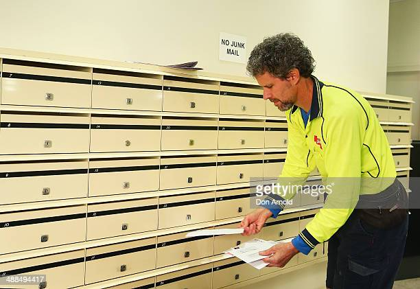A postman delivers mail to a building in Surry Hills on May 7 2014 in Sydney Australia Australia Post is considering a userpay mail delivery model as...