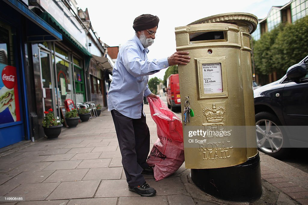 A postman empties a gold post box in Isleworth on August 6, 2012 in London, England. The post box was painted gold to celebrate British athlete Mo Farah's victory in the Men's 10,000m race at the London 2012 Olympic Games on Saturday and is located close to where Mo trained and went to school.