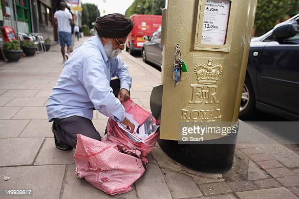 A postman empties a gold post box in Isleworth on August 6 2012 in London England The post box was painted gold to celebrate British athlete Mo...