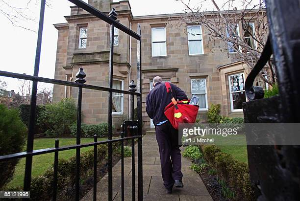 A postman makes a delivery at the Edinburgh home of the former chief executive of Royal Bank of Scotland Sir Fred Goodwin on February 26 2009 in...
