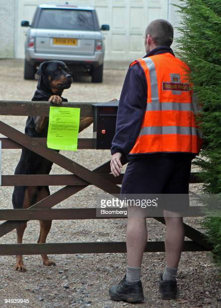 Postman Paul Haslegrave is greeted by a dog as he delivers letters on his rounds in Virginia Waters Surrey UK on Thursday Feb 26 2009 The leaders of...