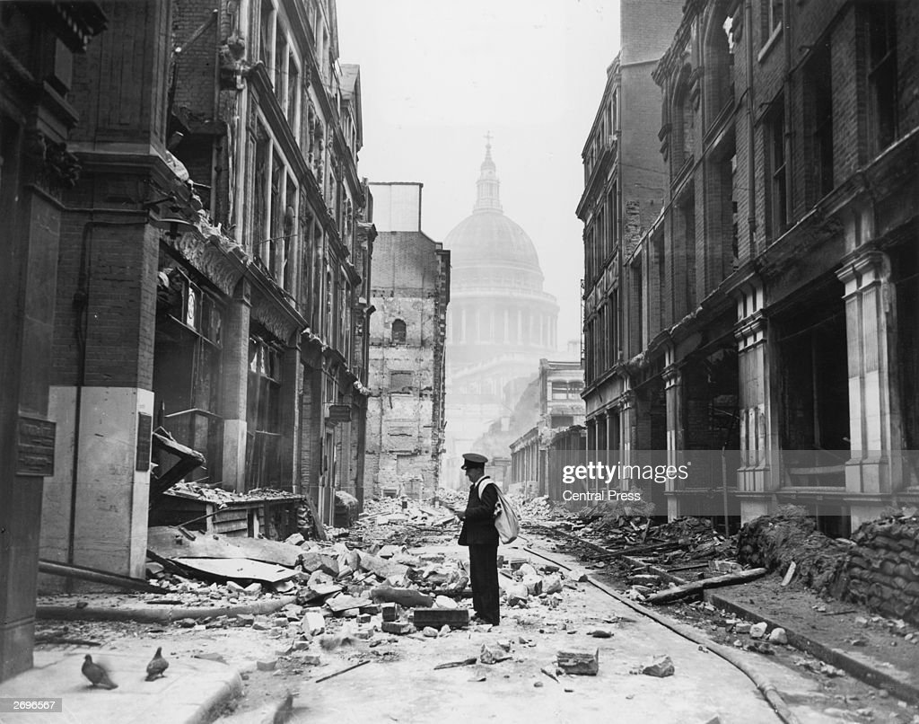 A postman tries to deliver letters to premises in Watling Street in the City, after a night time German air raid. The dome of St Paul's Cathedral is in the background.