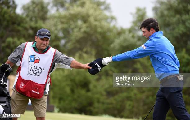 T Poston is handed his hat after the wind blew it off on the 15th tee during the third round of the Valero Texas Open at TPC San Antonio ATT Oaks...