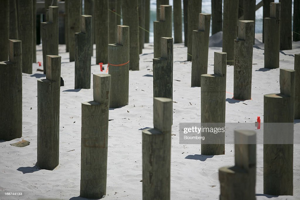 Posts sit buried in the sand to support the boardwalk in Seaside Heights, New Jersey, U.S., on Tuesday, May 14, 2013. Seaside Heights Mayor William Akers is looking forward to showing off the improvement as the prince visits, part of a week-long U.S. tour that also includes stops in Washington, Colorado and New York. Photographer: Scott Eells/Bloomberg via Getty Images