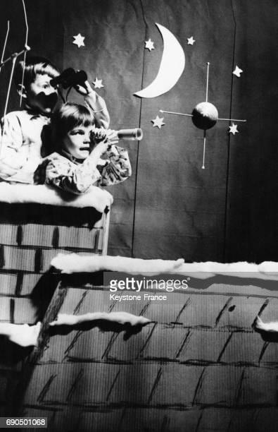 Postés sur la cheminée de leur maison et armés de jumelles et de longue vue ces enfants attendent avec impatience l'arrivée du Père Noël en France le...