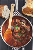 Pot of home made meatballs in sauce with parsley; wooden spoon; bread