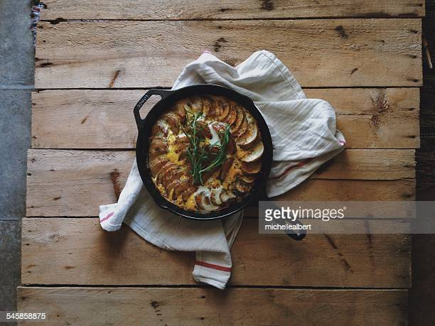 Potato and cheese frittata in skillet on wooden board