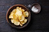 Homemade crispy Potato chips and sea salt on dark wooden background