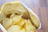 Potato chips in open snack bag close up on table floor