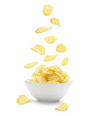 Potato chips falling in the faience white bowl. Isolated on white background