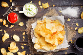 Potato chips with dipping sauces on a rustic table.