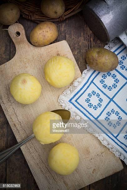 Potato dumplings on cutting board and potato ricer